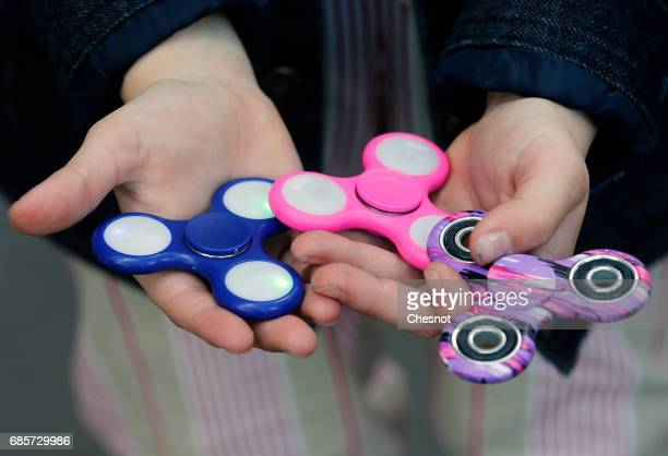 In this photo illustration a child shows a 'Hand Spinner' on May 20 2017 in Paris France The 'Hand Spinner' is a toy that sits like a propeller on a...