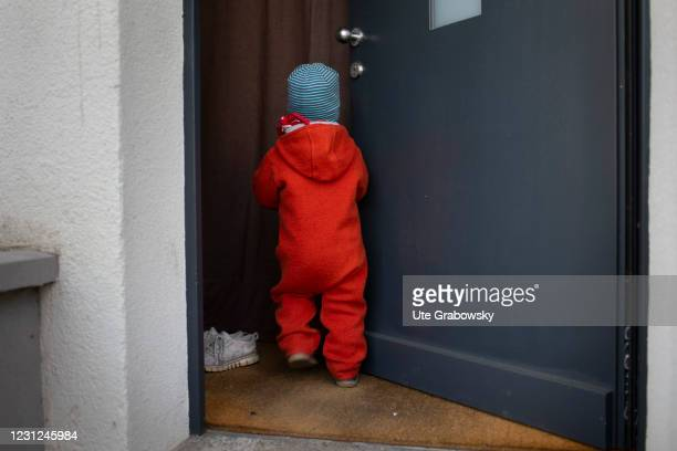 In this photo illustration a child walks into a front door on February 17, 2021 in Bonn, Germany.