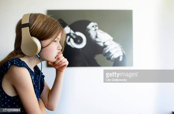 In this photo illustration a child with headphones is sitting in front of a picture of an ape on April 15 2020 in Bonn Germany