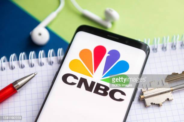 In this photo illustration, a CNBC logo seen displayed on a smartphone with a pen, key, book and headsets in the background.