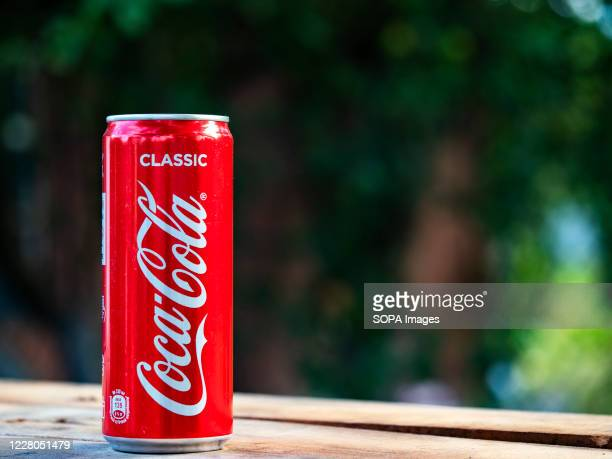 In this photo illustration a Coca-Cola can seen displayed on a table.