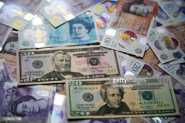 In this photo illustration, a collection of British five, ten and twenty pound sterling and twenty and fifty US dollar banknotes are seen displayed.