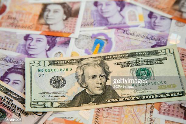 In this photo illustration, a collection of British ten and twenty pound sterling and twenty dollar banknotes are seen displayed.