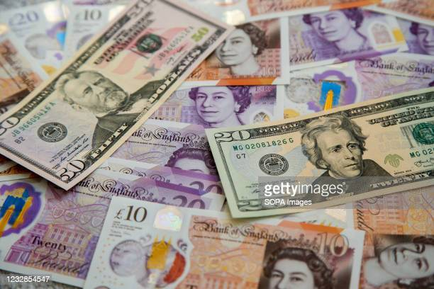In this photo illustration, a collection of British ten and twenty pound sterling and fifty and twenty dollar banknotes are seen displayed.