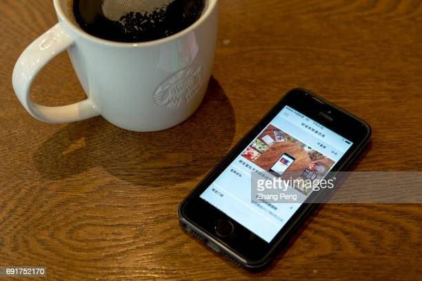 In this photo illustration a cup of Starbucks coffee and MSR account on a mobile phone In the second quarter of 2017 Starbucks opened its stores to...