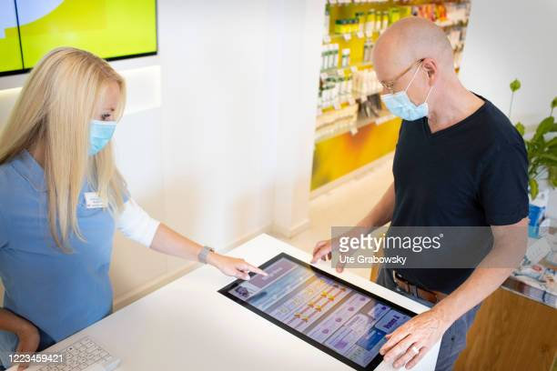 In this photo illustration a customer and a pharmacist in times of corona pandemic jointly select a product on a screen after consultation on June 12...