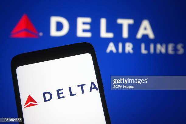 In this photo illustration a Delta Air Lines logo is seen on a smartphone and a pc screen.