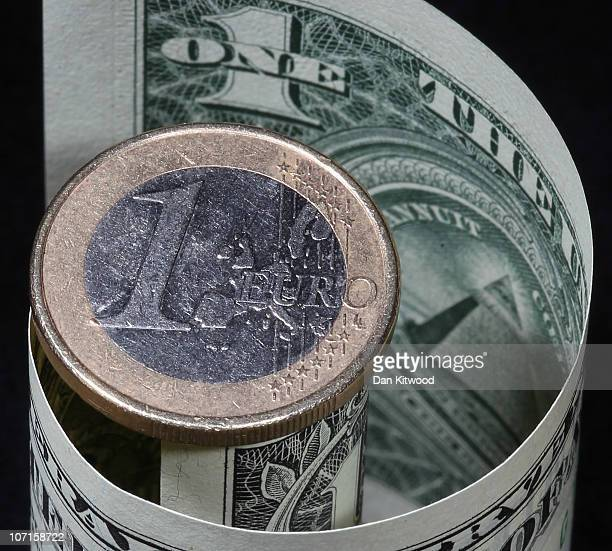 In this photo illustration a Euro coin rest on top of a Dollar note on November 26 2010 in London England Concerns over the Euro zone debts have...