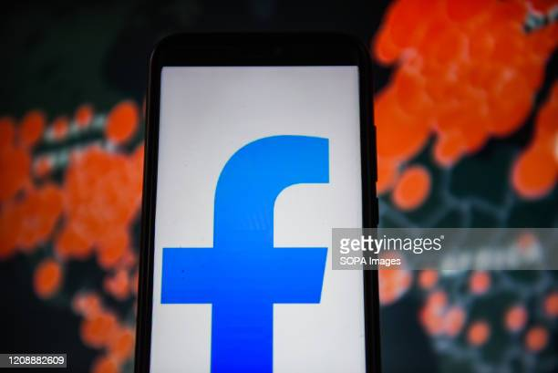 In this photo illustration a Facebook Lite logo is seen displayed on a smartphone with a World map of COVID 19 epidemic on the background.