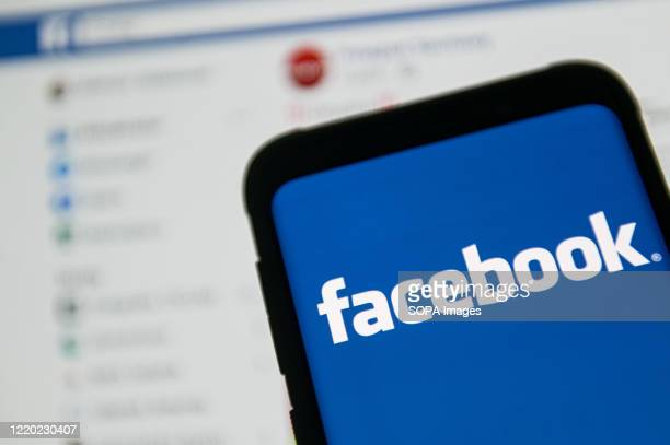 In this photo illustration a Facebook logo seen displayed on a smartphone