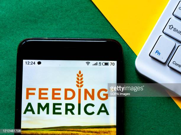 In this photo illustration a Feeding America logo seen displayed on a smartphone