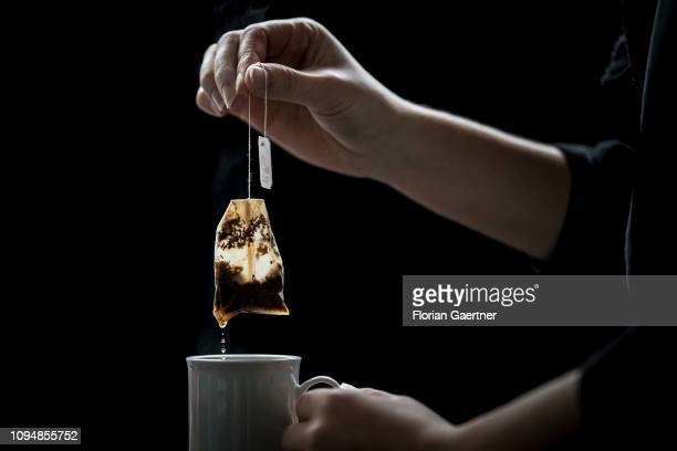 In this photo illustration a female person holds a tea bag above a cup of tea on February 05 2019 in Berlin Germany