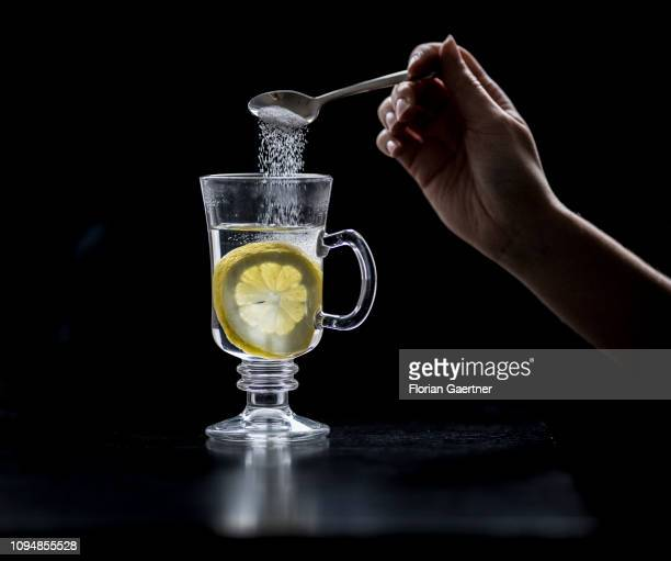In this photo illustration a female person puts sugar into a glas of hot lemon on February 05, 2019 in Berlin, Germany.