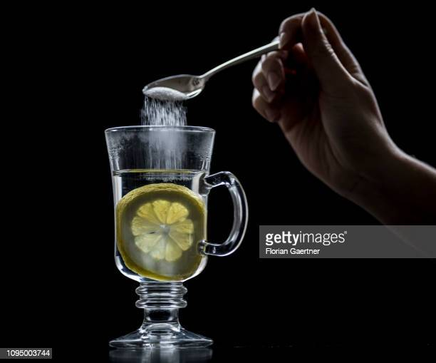 In this photo illustration a female person puts sugar into a glas of hot lemon on February 05 2019 in Berlin Germany
