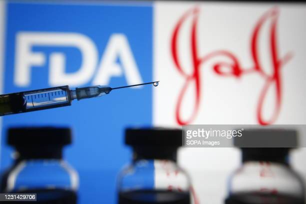In this photo illustration a Food and Drug Administration and Johnson & Johnson logos are seen behind a medical syringe and vials.