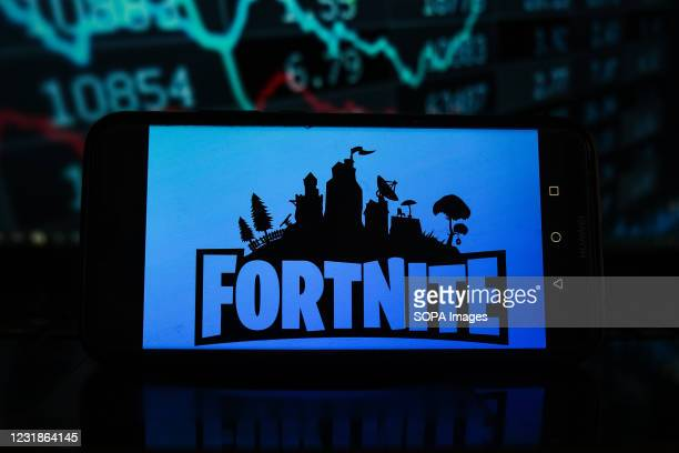 In this photo illustration a Fortnite logo seen displayed on a smartphone with stock market percentages in the background.