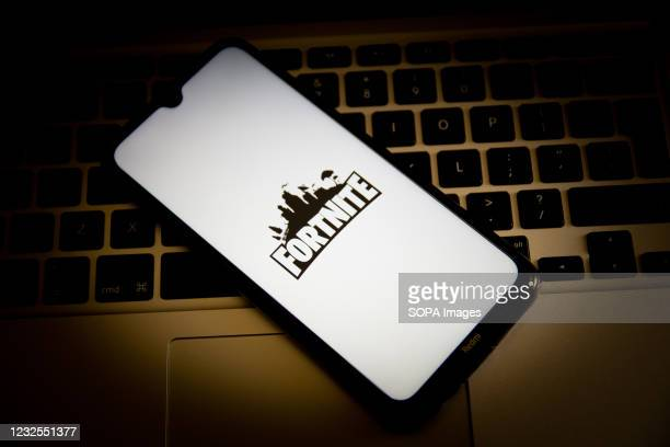 In this photo illustration, a Fortnite logo seen displayed on a smartphone screen with a computer keyboard in the background.