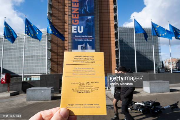 In this photo illustration, a French passport and an International Certificate of Vaccination or Prophylax is shown in front of the Berlaymont, the...