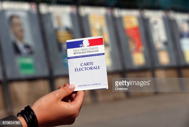 In this photo illustration a French voter registration card is seen in front of official campaign posters for all eleven candidates for the 2017...