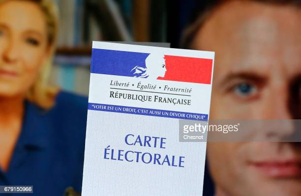 In this photo illustration a French voter registration card is seen in front of official campaign posters of candidates in the French presidential...