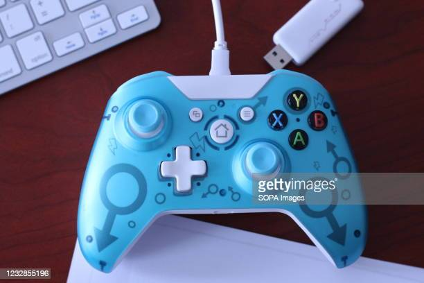 In this photo illustration, a generic controller for Microsoft Xbox 360 game system and its USB dongle are displayed on a table with various...