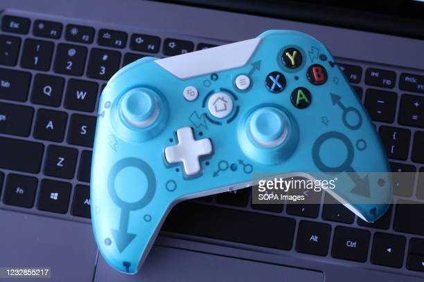 In this photo illustration, a generic controller for Microsoft Xbox 360 game system is displayed on the keyboard of a laptop.