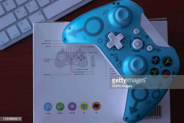 In this photo illustration, a generic controller for Microsoft Xbox 360 game system is displayed on its original box with a keyboard in the...