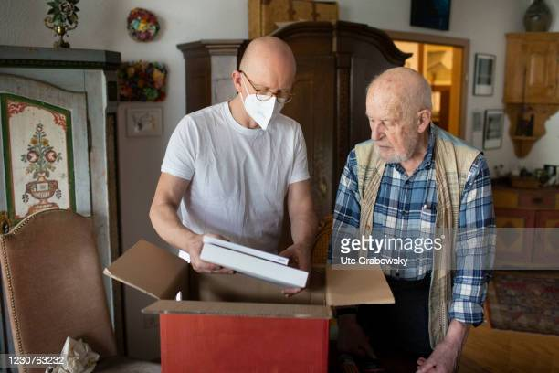 In this photo illustration a geriatric nurse helps an old man to pack a moving box on January 23, 2021 in Heidelberg, Germany.