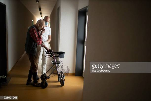 In this photo illustration A geriatric nurse helps an old man with a walker on June 11 2020 in Bonn Germany