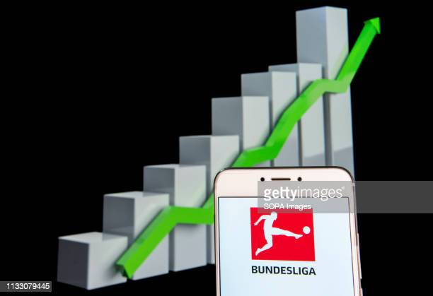In this photo illustration a German professional association football league Bundesliga logo is seen on an android mobile device with an ascent...