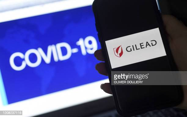 In this photo illustration a Gilead logo is displayed on a smartphone next to a screen showing a COVID-19 graphic on March 25, 2020 in Arlington,...