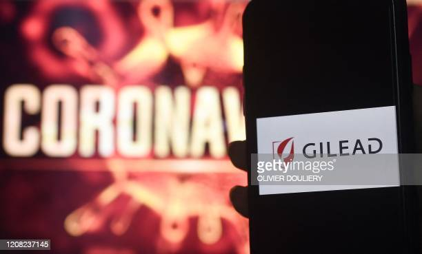In this photo illustration a Gilead logo is displayed on a smartphone next to a screen showing a coronavirus graphic on March 25, 2020 in Arlington,...