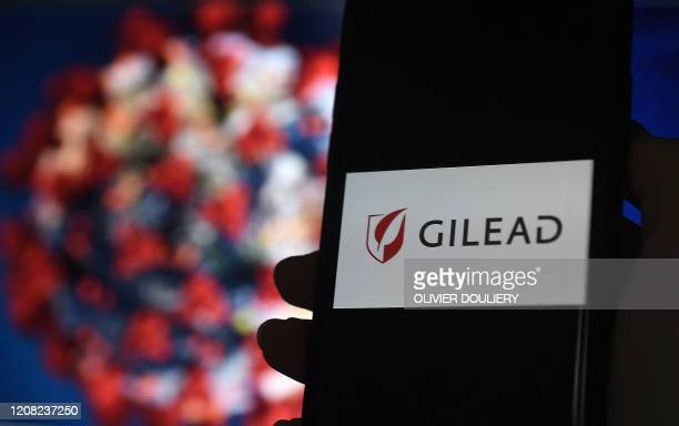 In this photo illustration a Gilead logo is displayed on a smartphone photographed on coronavirus COVID-19 illustration graphic background on March...