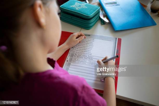 In this photo illustration a girl is doing her homework learning how to write on May 19 2020 in Bonn Germany