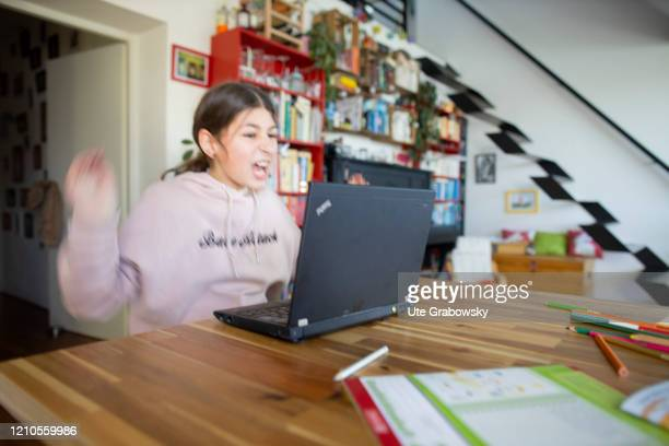 In this photo illustration a girl is overwhelmed in front of her laptop on April 15, 2020 in Bonn, Germany.