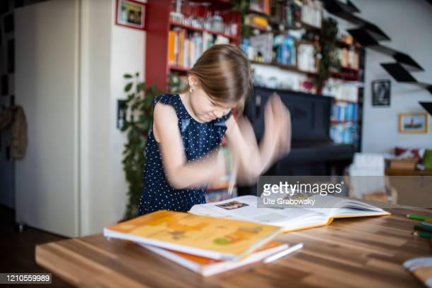 In this photo illustration a girl is overwhelmed in front of her homework on April 15, 2020 in Bonn, Germany.