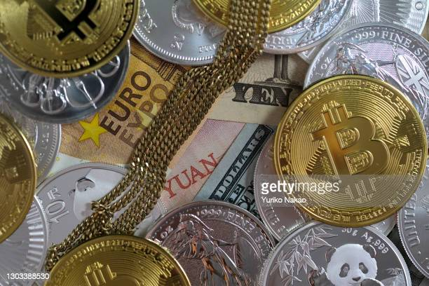 In this photo illustration, a gold necklace, one-ounce silver bullion coins, visual representations of the digital cryptocurrency, Bitcoin are placed...
