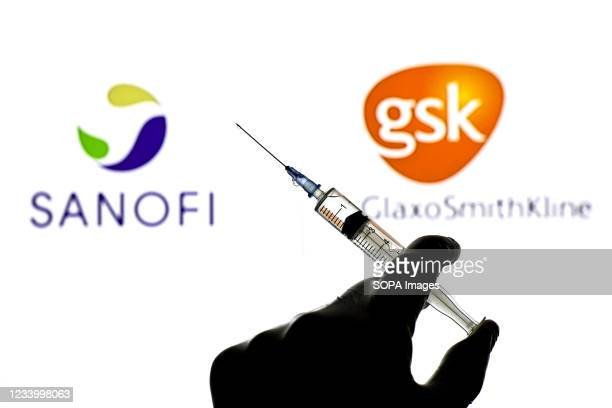 In this photo illustration a hand holding a medical syringe seen in front of the Sanofi and GlaxoSmithKline logo.