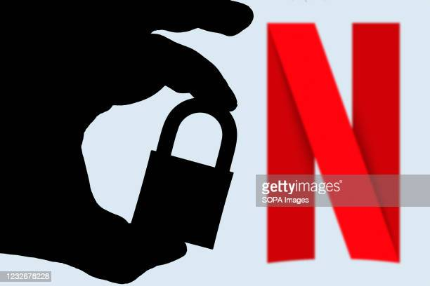 In this photo illustration a hand seen holding a padlock and in the background the logo of Netflix on the computer screen. Online data protection -...