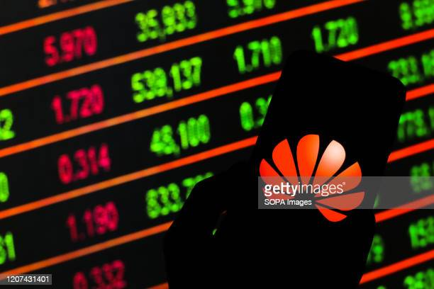 In this photo illustration a Huawei logo seen displayed on a smartphone Stock market prices in the background as stock markets tumble all over the...