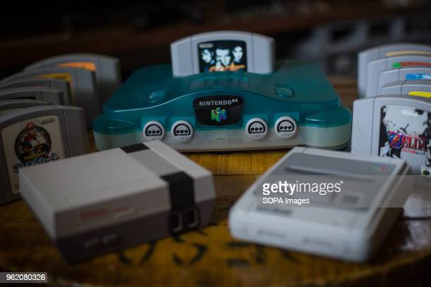 Japanese edition of the Nintendo 64 clear blue version with a bunch of games next to a Nintendo Classic Mini 'Nintendo Entertainment System' and a...