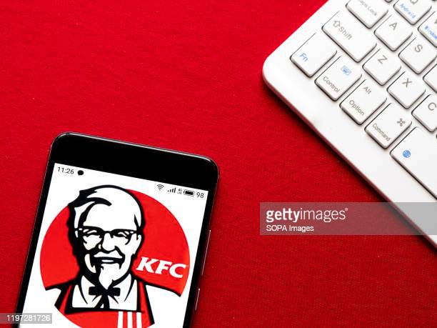 In this photo illustration a KFC logo seen displayed on a smartphone