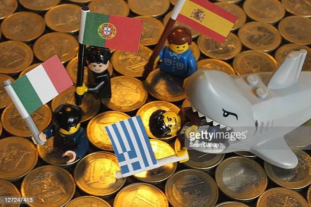 In this photo illustration a Lego shark chomps down on a Lego figure holding a Greek flag as other figures holding an Italian Portuguese and Spanish...