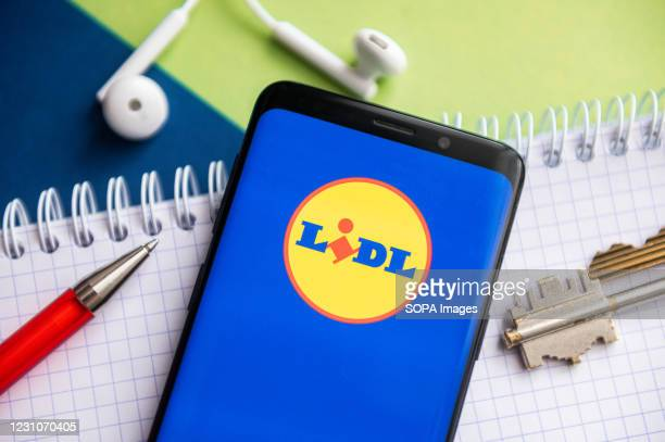 In this photo illustration, a Lidl logo seen displayed on a smartphone with a pen, key, book and headsets in the background.