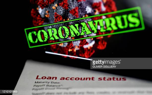 """In this photo illustration, a loan statement account status is displayed next a iPhone screen behind reading """"coronavirus"""" on April 16 in Arlington,..."""