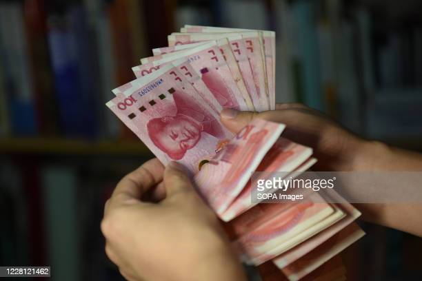 In this photo illustration a man counts 100 RMB notes. In recent years, China has clamped down on shadow banking,concerned about the hidden risks in...