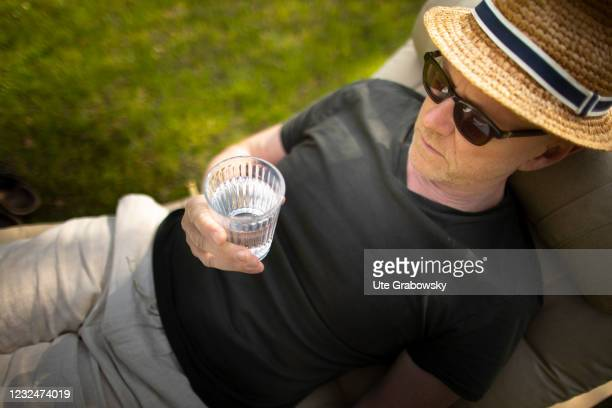 In this photo illustration a man drinks some water relaxing on a lounger on April 20, 2021 in Bonn, Germany.