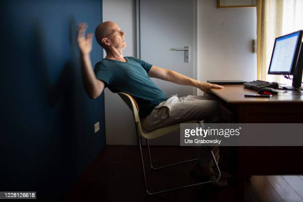 In this photo illustration a man falls off his chair in the home office on August 19 2020 in Bonn Germany