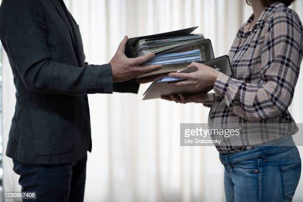 In this photo illustration a man gives a few folders to a pregnant woman at work on January 17, 2021 in Bonn, Germany.