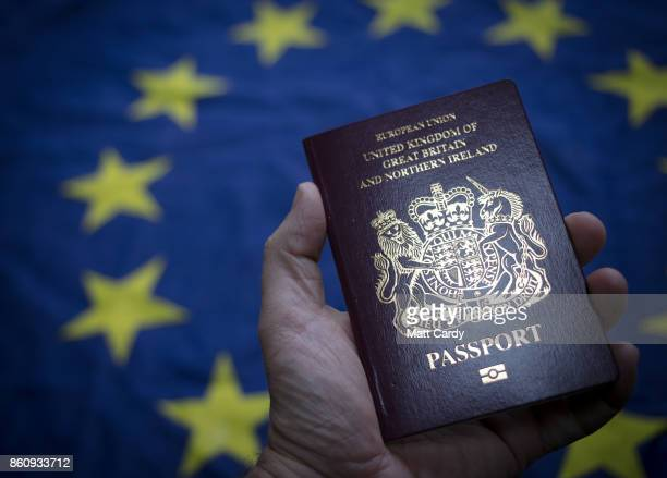 In this photo illustration a man holds a British passport in front of the flag of the European Union on October 13 2017 in Bath England Currency...